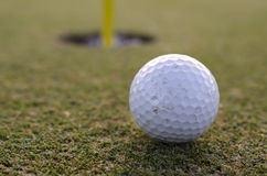 Golf ball close to hole on putting green Stock Photo