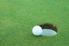 Golf ball close to hole. A golf ball very close to a hole Royalty Free Stock Photo