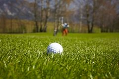 Golf ball close-up with golfer man Stock Photos