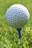 Golf ball. Close-up of golf ball resting on blue tee with grass and space for copy royalty free stock images