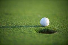 Golf ball close up. White golf ball on green field close up Stock Photos