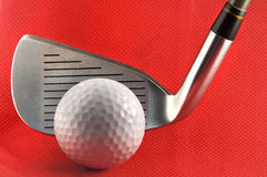Golf ball and club. Picture of a golf ball with a iron club with red background Stock Image