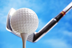 Golf ball and club. Golf club and golf ball about to tee off against a blue sky stock photography