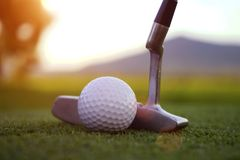 Golf ball and golf club in beautiful golf course at sunset background. Golf ball on green in golf course at Thailand royalty free stock photos