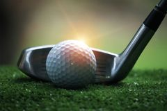 Golf ball and golf club in beautiful golf course at sunset background. Golf ball on green in golf course at Thailand. Golf ball and golf club in beautiful golf stock photo