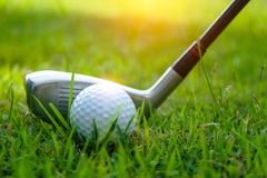 Golf ball and golf club in beautiful golf course at Thailand. Collection of golf equipment resting on green grass with green. Golf ball and golf club in royalty free stock photos