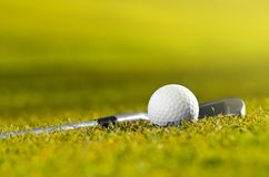 Golf ball and club on grass stock photo