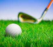 Golf ball with club in grass field. 3D render of a golf ball in grass field with out of focus club to the back Royalty Free Stock Image