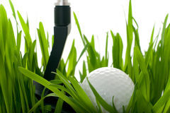 Golf ball with club on grass - isolated. Golf ball on green grass isolated on white royalty free stock image