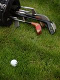 Golf Ball & Clubs in Rough. Golf ball lays in rough grass with older set of clubs in bag behind Royalty Free Stock Images