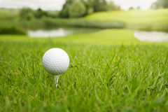 Golf ball at the course. Golf ball on a tee against the golf course with copy space royalty free stock photo