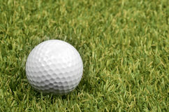 Golf ball on course with green grass. Royalty Free Stock Photography