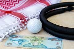 Golf Ball, Dirham Banknote, and Traditional Arab Male Clothes - kaffiyah and agal