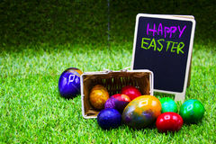 Golf ball with Easter eggs on green grass Royalty Free Stock Photos