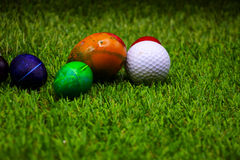 Golf ball with Easter eggs on green grass Stock Photo