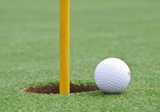 Golf ball on the edge of the cup Royalty Free Stock Photography