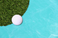 Golf ball edge of grass field Stock Photo