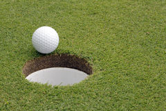 Golf Ball on Edge of Hole Royalty Free Stock Photography