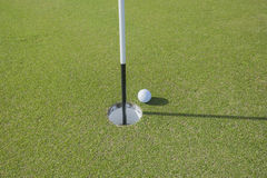 Golf ball at edge of hole Stock Images