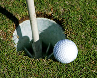 Almost. Golf Ball on the edge of a hole Stock Image