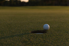 Golf ball on edge of  the hole Royalty Free Stock Image