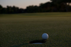 Golf ball on edge of  the hole Royalty Free Stock Photo