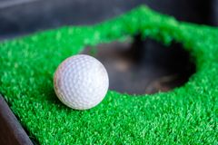 Golf ball edge hole cup on lawn. Golf ball edge hole cup on green lawn Stock Photo
