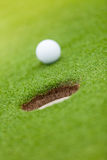 Golf ball on the edge of hole Royalty Free Stock Image