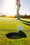Golf ball at the edge of hole with player in background Royalty Free Stock Photos
