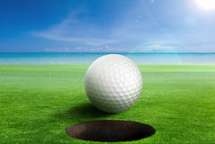 Golf Ball on edge of the hole. Shallow depth of field. Focus on the ball and the hole Royalty Free Stock Photography