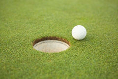 Golf ball at the edge of the hole Royalty Free Stock Photos