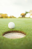 Golf ball at the edge of the hole. On a sunny day at the golf course Stock Photo
