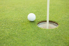 Golf ball at the edge of the hole Stock Photography