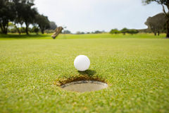 Golf ball at the edge of the hole Royalty Free Stock Photo