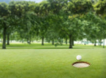 Golf ball at the edge of the hole Stock Photo