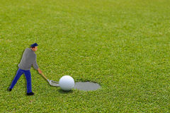 Golf ball at the edge of putting cup with a help from miniature Royalty Free Stock Photos