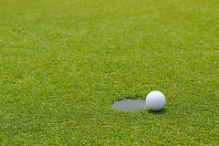 Golf ball at the edge of putting cup hold at putting green Stock Photos