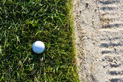 Golf ball on the edge of the sand bunker Stock Photography