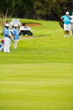 Golf Ball on Fairway. Generic image of a golf ball sitting in the middle of a fairway. With a few of the tournament marshals, in soft focus, in the background Royalty Free Stock Image