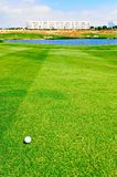 Golf ball on fairway with water hazard in front of green. Every golfers Nightmare, the golf ball on fairway with a large water hazard in front of the green on stock photo