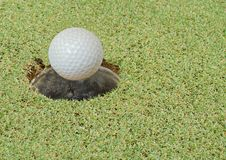 Golf ball falling to hole in course field stock photo
