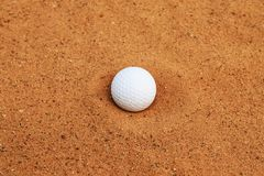 The golf ball falls into the sand pit. stock photography