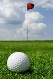 Golf ball and flag Stock Photography