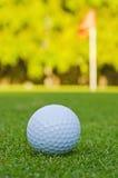 Golf ball and flag Stock Photo