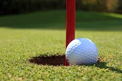 Golf ball and flag in hole Stock Photography