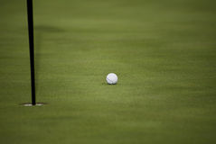 Golf Ball, Flag Pin, Hole, Green. Golf ball, has come to rest just before the hole Stock Photo