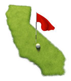 Golf ball and flag pole on course putting green shaped like the state of California Royalty Free Stock Images