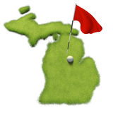 Golf ball and flag pole on course putting green shaped like the state of Michigan Royalty Free Stock Photography