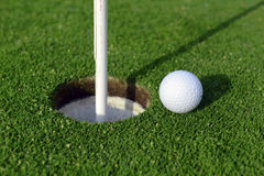 Golf ball and Flagstick of  Manicured grass of putting green. Of golf course Stock Photos
