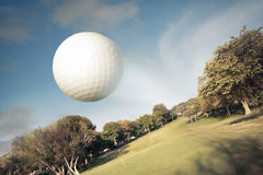 Golf ball flying over the field. Golf ball flying over green field royalty free stock photography